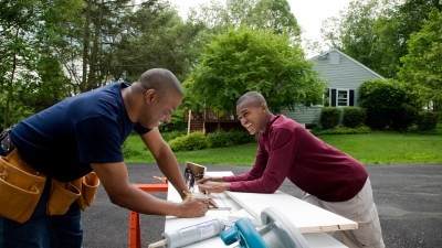 A father and son working on their house, father supporting not enabling his son