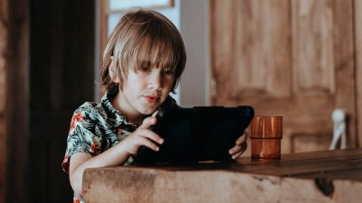 A boy uses an iPad at a table as part of his summer media diet