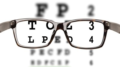 Glasses held in front of a chart used to test for vision problems, which often co-occur with ADHD