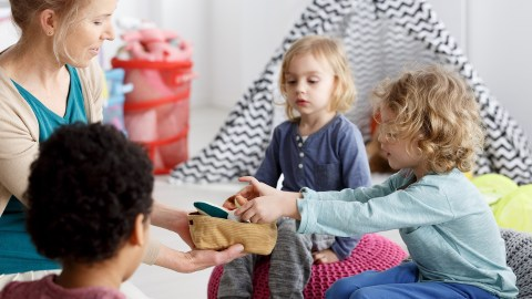 Little kids with ADHD and their mothercleaning toys after play
