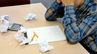 A freshman with ADHD, crumpling up his homework in frustration during the second semester of the year