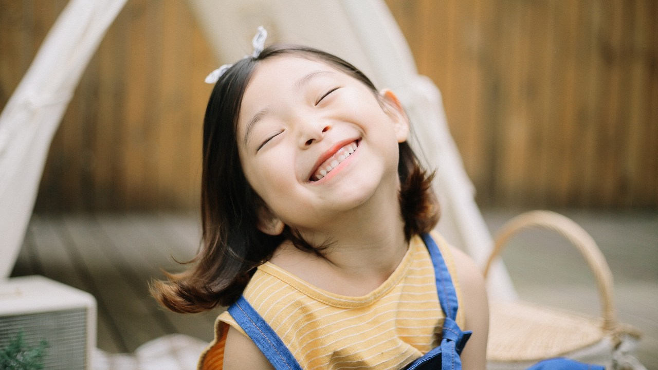 A girl with ADHD smiles because her parents use positive parenting techniques.