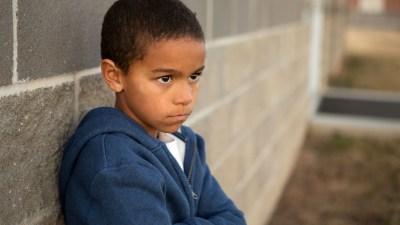 Upset ADHD boy leans against a wall