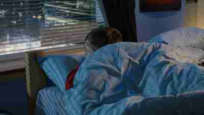 Medium shot of a boy looking out window while lying in bed and trying to fall asleep