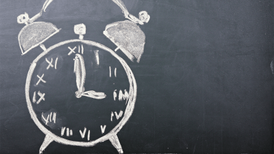 An alarm clock, a tool for teaching time management to children with ADHD, drawn in chalk on a blackboard