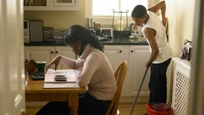 a mom with ADHD pays bills while her son mops the floor, both get things done using the body double technique