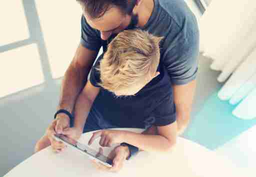 Young ADHD boy sitting with father and touching screen of pc