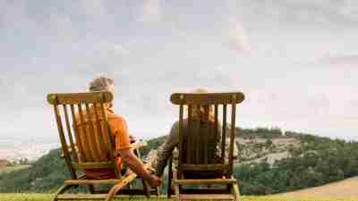 A couple sitting in chairs looking out at a green landscape
