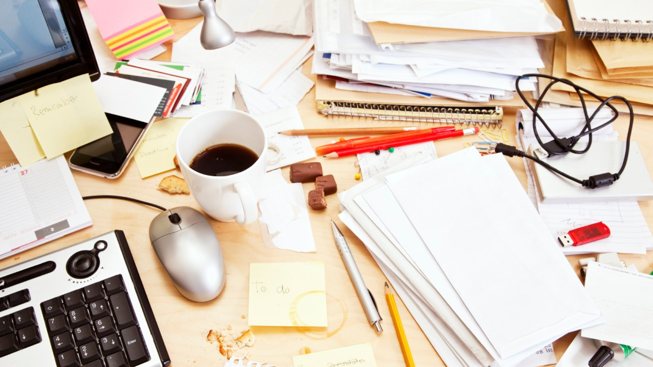 "A messy desk of someone with ADHD wondering, ""Am I going to get fired for being disorganized?"""
