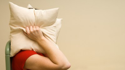 Person with hypersensitivity and ADHD covering their head with pillows