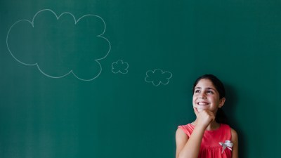 student with ADHD thinking about goals by chalkboard in a classroom
