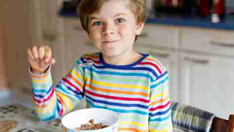 Boy with ADHD eating cereal — a quick breakfast to smooth the morning routine.