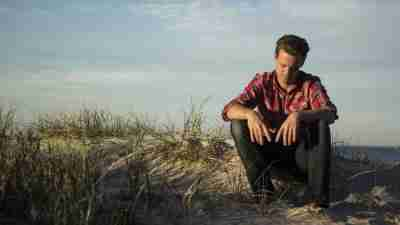 Man with ADHD sits on hill by beach looking sad as he considers going to cognitive therapy