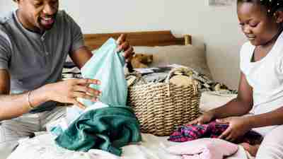 Father and daughter with ADHD folding laundry and doing chores together