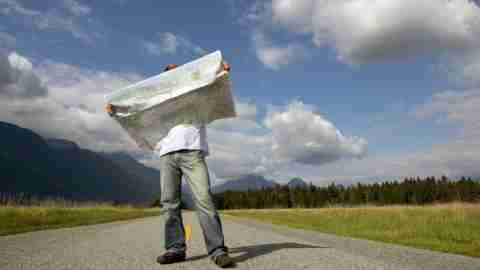 Man with ADHD standing on road holding map with mountains behind him