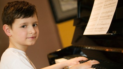 Young boy with ADHD playing piano