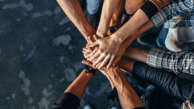 A group of people stacking their hands on top of the other to symbolize teamwork.