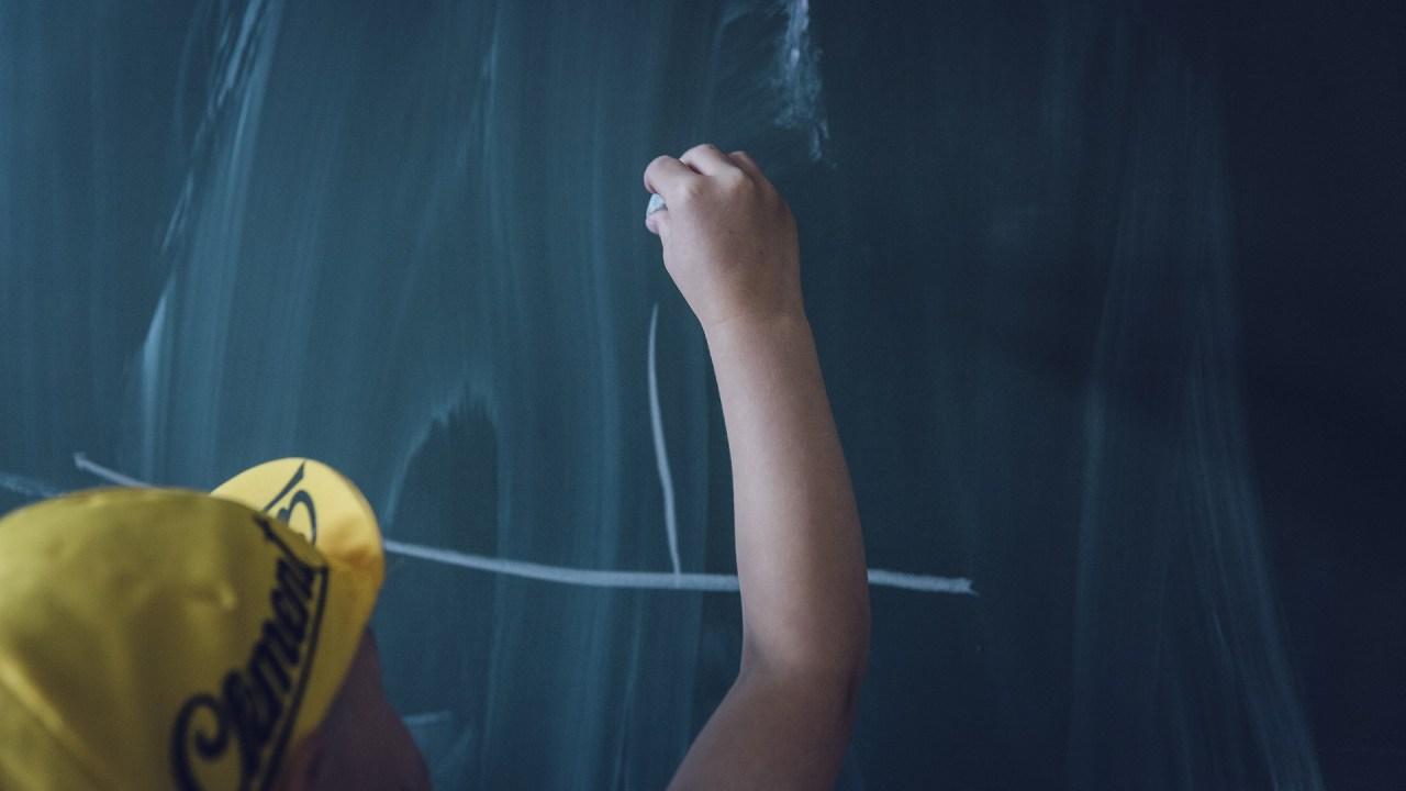 ADHD boy writing on a school chalk board