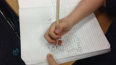 ADHD boy has bad classroom behavior and doodles in his notebook instead of taking notes at school