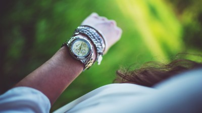 A woman with ADHD looks at her watch and ponders the hardest challenges of living with ADHD