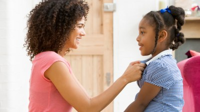 A mom helps her daughter get dressed for school as part of her morning routine