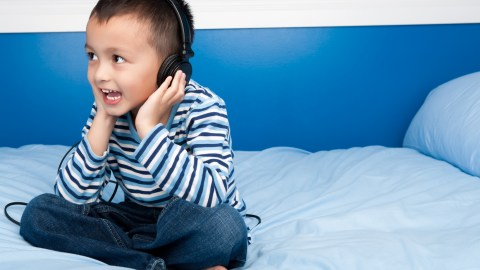 A boy with ADHD listens to headphones.