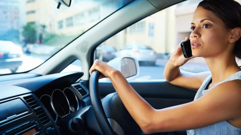 Woman driving and on the phone illustrates the ability to multi-task -- one of your executive functions.