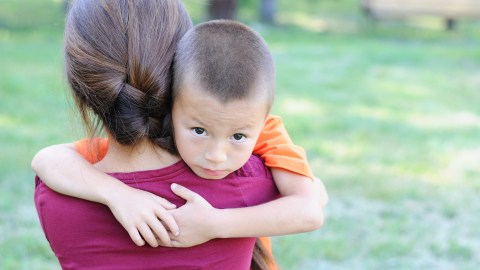 A young child hugging his mother and exhibiting strong signs of anxiety.