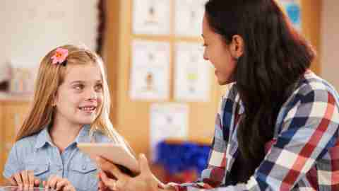A teacher helps a student one on one, a smart strategy to help adhd students.