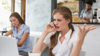 Annoyed ADHD woman using mobile phone in coffee shop