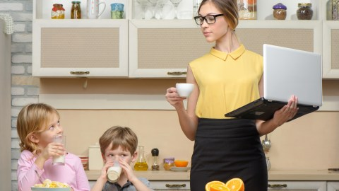 A woman looks up healthy meal ideas while preparing breakfast for her children.