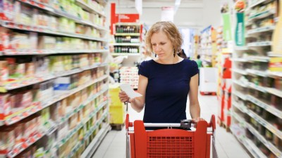 A woman grocery shopping, looking at her meal planning schedule for the week ahead