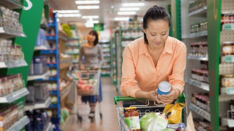 A woman reading the label on a can of food at the supermarket to see if it can be cooked easily or fits in with her meal plan
