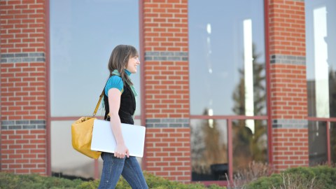A college student with ADHD walks across campus carrying her laptop