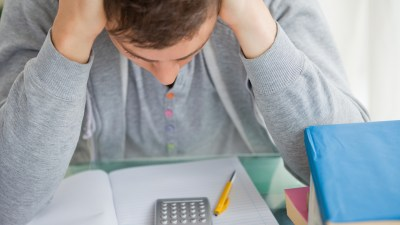 A college student with ADHD and symptoms of dyscalculia is frustrated while working on a math assignment.