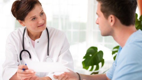 A college student discusses medication schedules with his doctor, a good college survival tip.