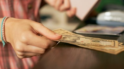 A college student with ADHD sorting her money, a smart tip for young adults