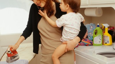 A mom holds her child while also ironing — multitasking is a strength for those with ADHD.