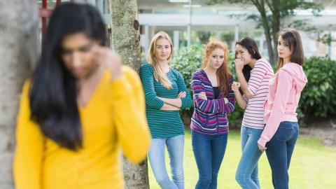 A girl with social anxiety disorder looks sad while a group of girls talk about her.