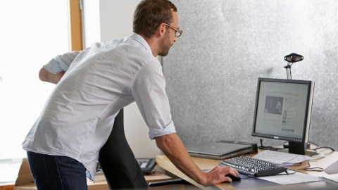 An employee maintains his attention by standing, helping master his ADHD in the workplace.