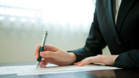 A businesswoman signs a document while keeping her desk clutter free, a good way to manage ADHD in the workplace.