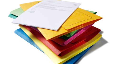A stack of color coded folders to be used for documents of differing degrees of importance, a good strategy for controlling ADHD in the workplace.