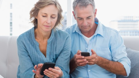 A couple using smart phones to record ideas and tasks, simpliflying their lives.