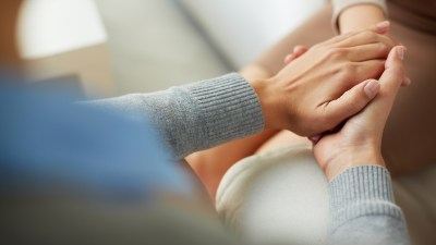 People hold hands to show compassion after being sensitive to criticism.