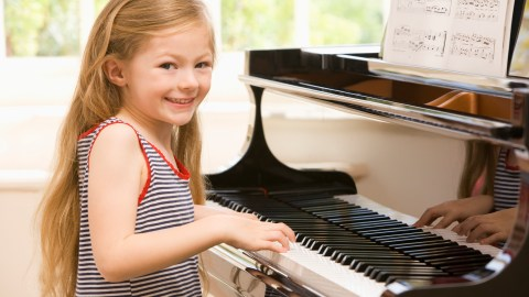 Girl Playing Piano. Many piano concertos are used in music therapy for children with ADHD.