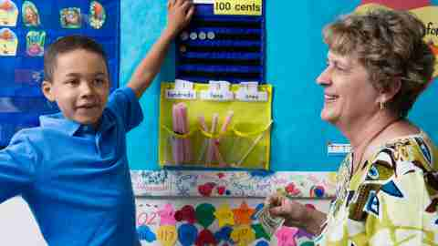 A student and teacher practice math skills at an activity board