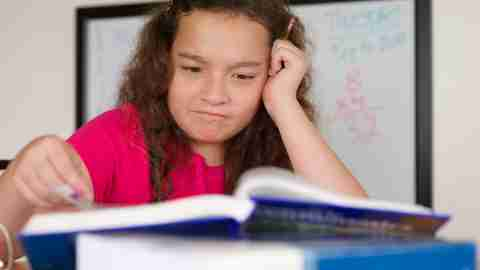A girl reading a textbook about how to improve math skills