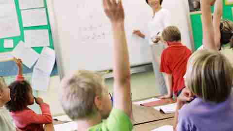 A teacher giving a lesson on how to improve math skills while students raise their hands