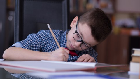 A boy does homework to imrpove math skills