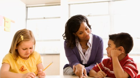 A teacher helps her student improve math skills with a worksheet